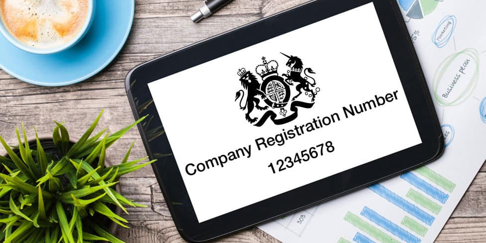 An iPad lying on a desk with the screen displaying the text Company Registration Number 12345678 and the Companies House logo.