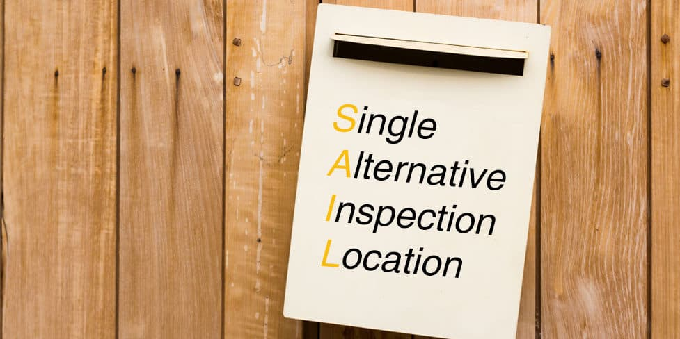 Sign hanging on door displaying SAIL and Single Alternative Inspection Location.