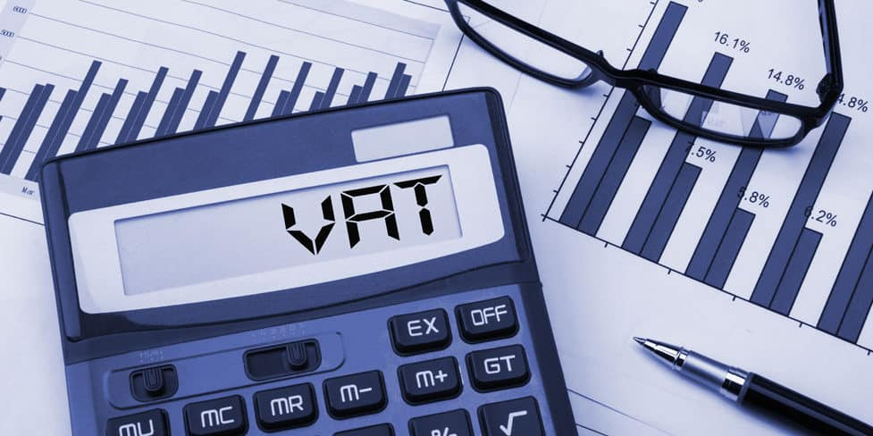 Electronic VAT calculator on desk with paperwork displaying financial graphs.