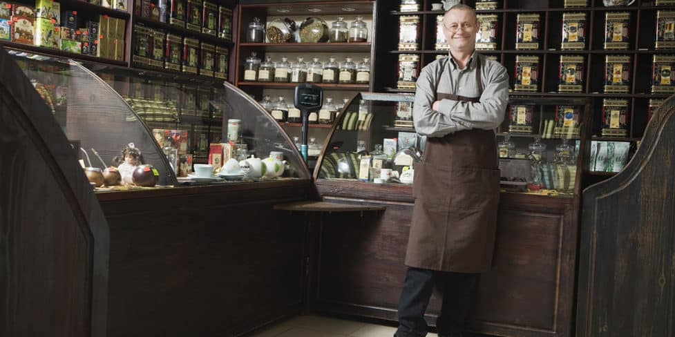 Image of a shop owner standing in an old-fashioned general store, illustrating the notion of deciding to sell your limited company
