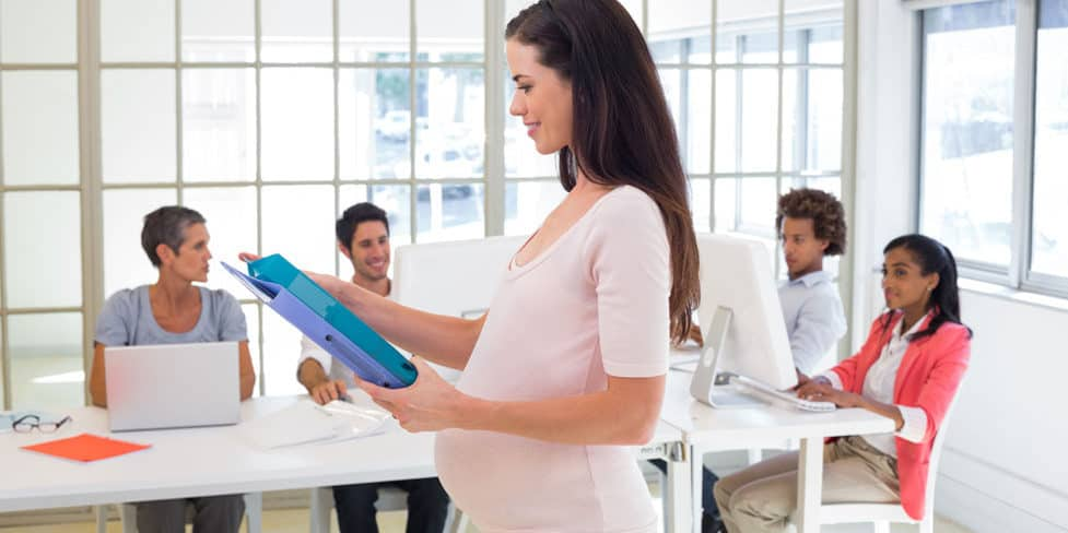 A pregnant businessperson working in a modern office.