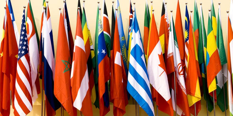 A row of different country flags standing upright against a wall.