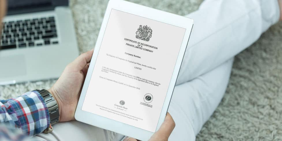 Person reading an iPad with screen displaying a certificate of incorporation.
