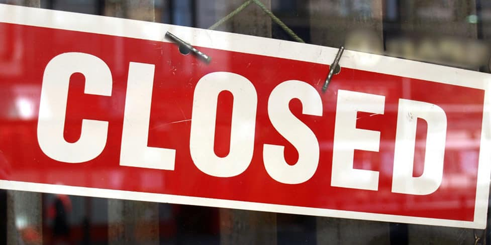 A rectangular 'closed' sign with white lettering on a red background, hanging in a shop window, used to represent the process of dissolving a limited company.