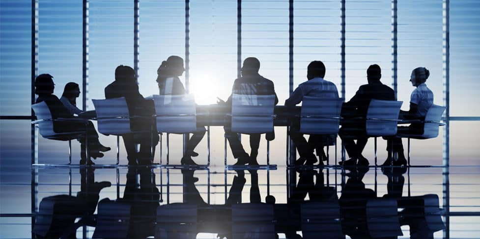 Image of a group of business people sitting around a large table, illustrating the concept of taking minutes of the first board meeting of directors.