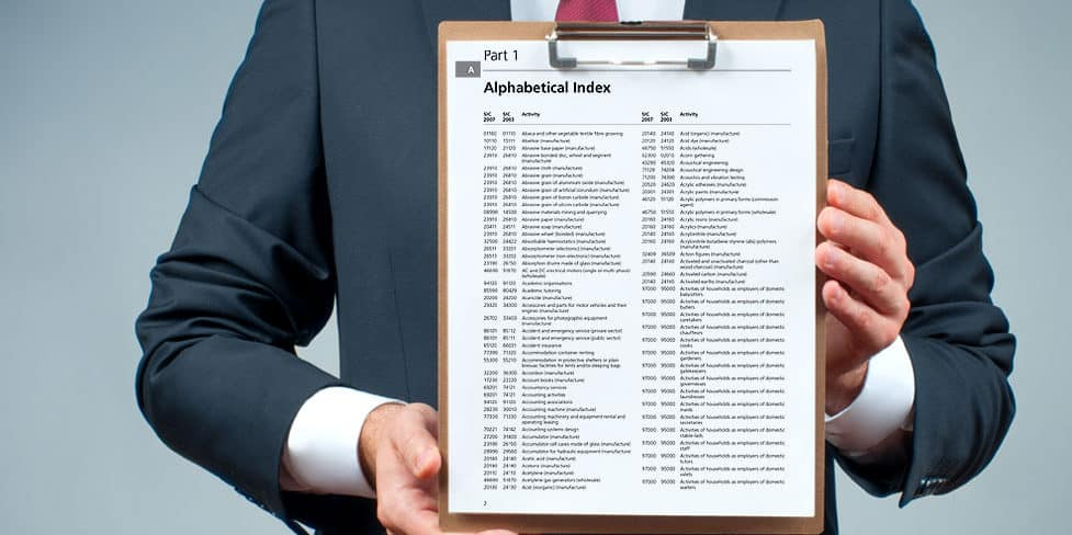 A man in a suit holding a clipboard displaying a list of limited company SIC codes in alphabetical order.