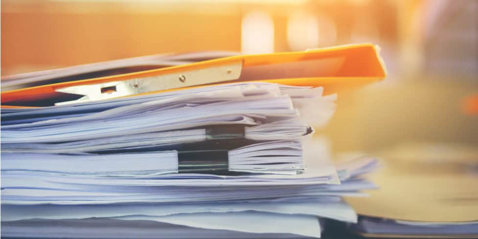 Image of a pile of documents and files sitting on top of a desk, illustrating the requirement to keep limited company records