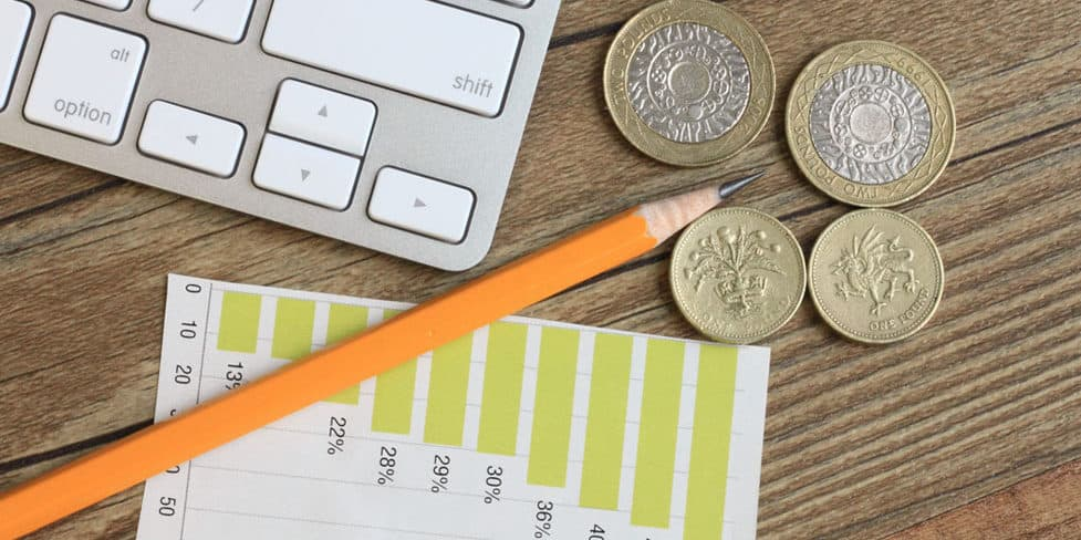 Coins, a pencil, laptop and financial chart sitting on a desktop representing the process of preparing annual accounts.