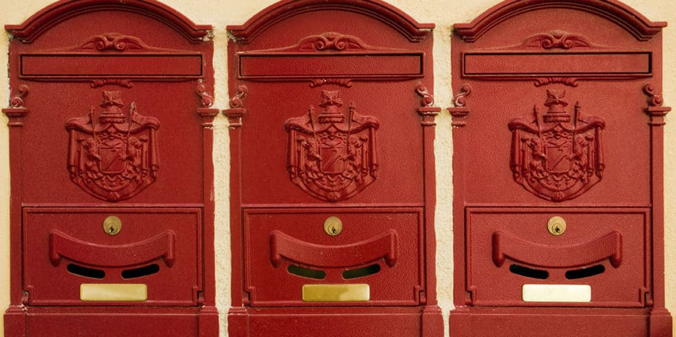 An image of three red Victorian Royal Mail post boxes mounted on a wall, representing the primary purpose of a registered office as a postal address.