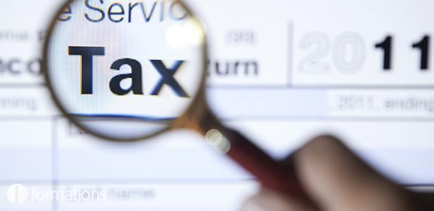 """Close-up of a screenshot of the HMRC website, in which someone is holding a magnifying glass over the word """"tax""""."""