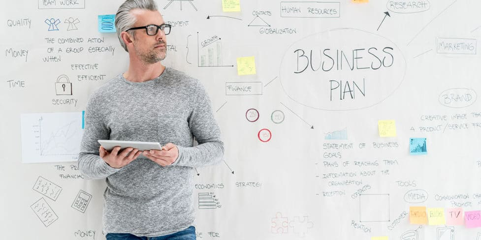 A man standing in front white wall adorned with writing and brainstorming ideas relating to a business plan.