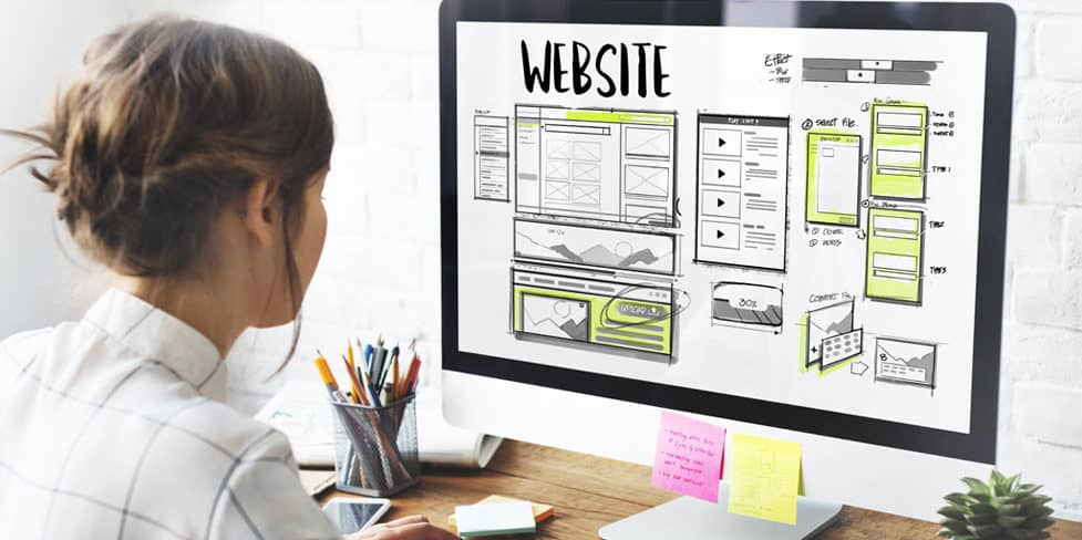 Business person designing a company website on her computer monitor that displays the heading ' Website' above webpage layouts and mock ups.
