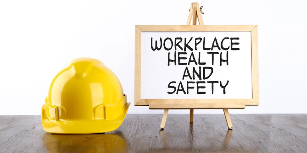 Picture of a yellow hard hat next to a small easel that is supporting a framed board displaying the words 'Workplace Health and Safety'.