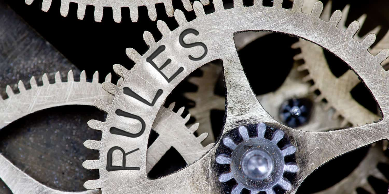 The internal workings of a clock with 'RULES' stamped on a cog wheel, illustrating the concept of articles of association