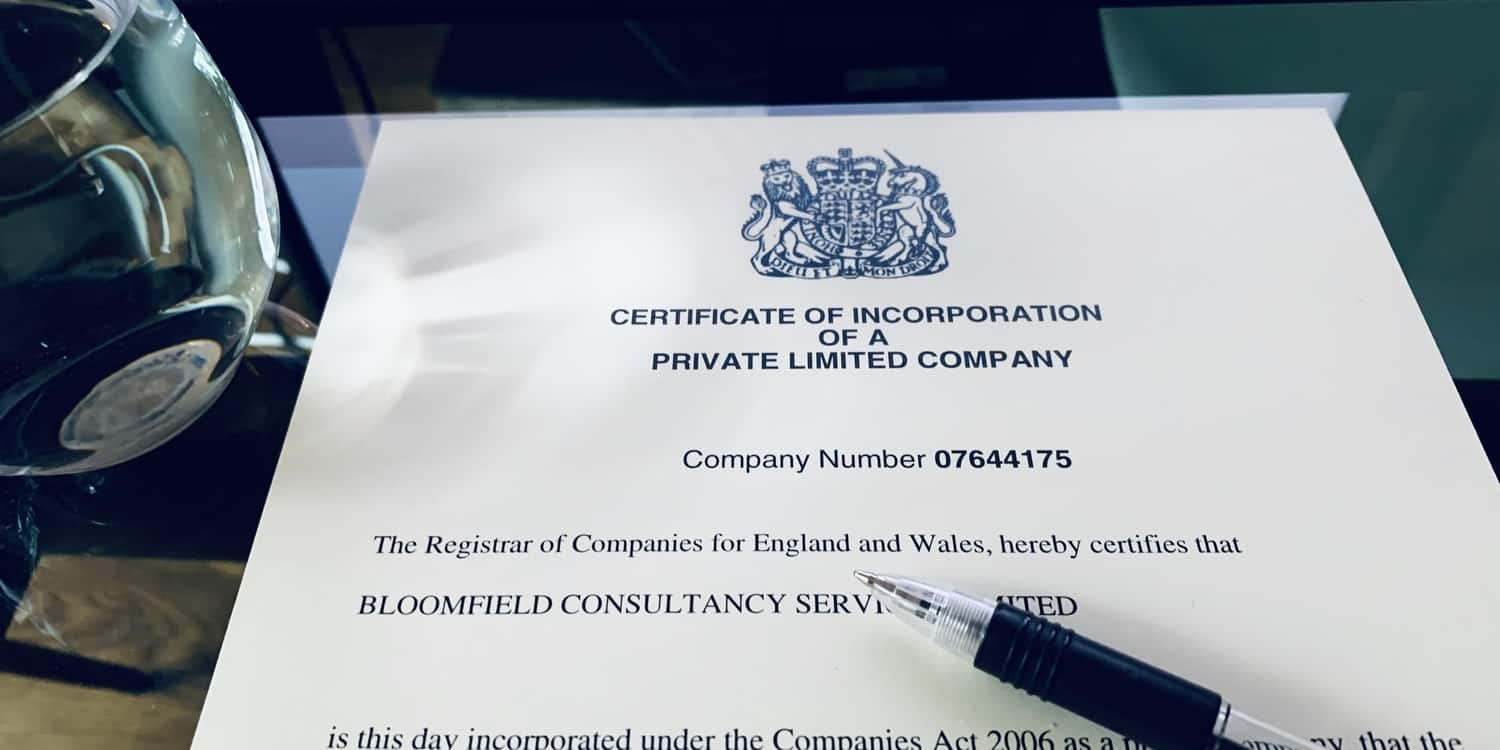 A certificate of incorporation lying on a desk with pen and glass of water.