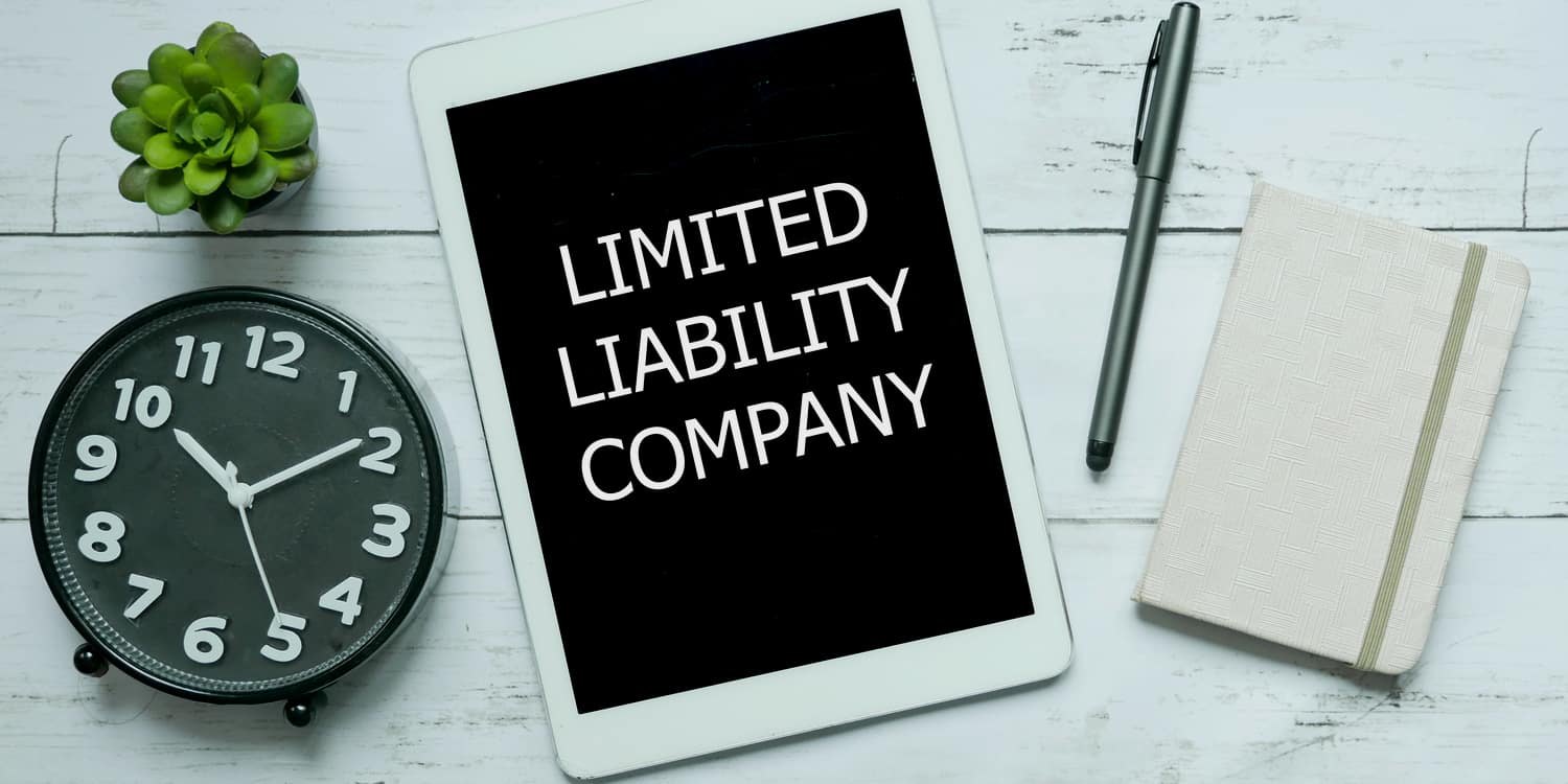 'LIMITED LIABILITY COMPANY' headline displayed on a white ipad sitting on a desktop with clock, pen and notebook.