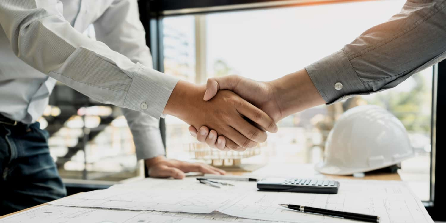 Two business people shaking hands over a desk with documents pens and calculator.