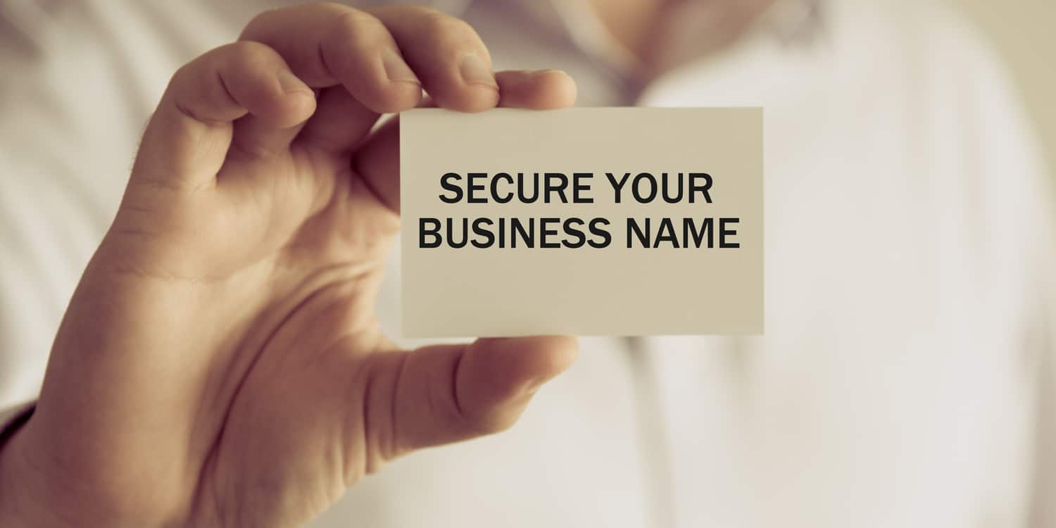 "Businessman holding a white card with ""SECURE A BUSINESS NAME"" displayed in black font."