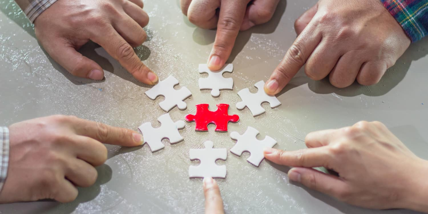 A red jigsaw piece surrounded by 4 white jigsaw pieces, illustrating the concept of a holding company.