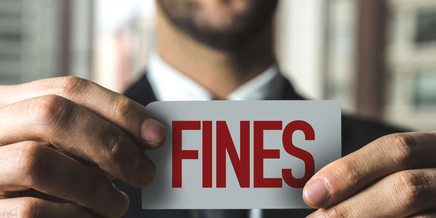 Businessman holding up a white card that displays the word 'FINES' in red text.