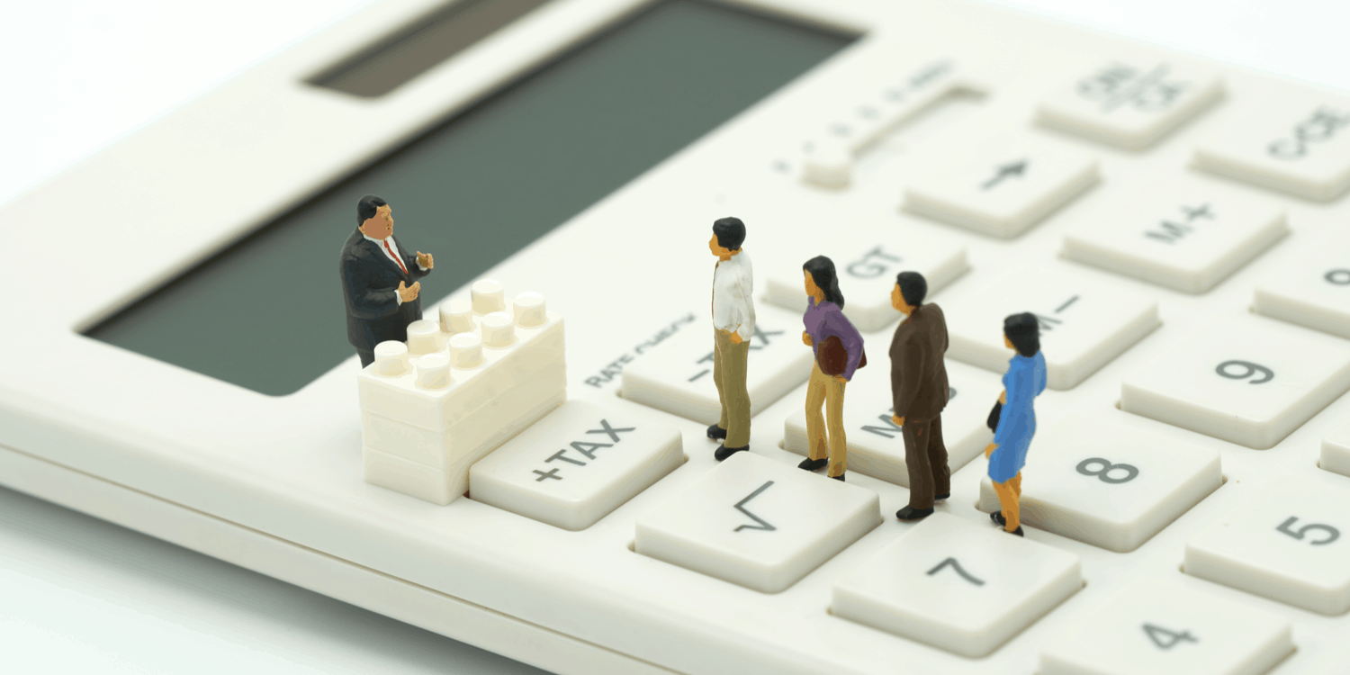 Miniature people standing in a line on a desktop calculator waiting to pay tax.