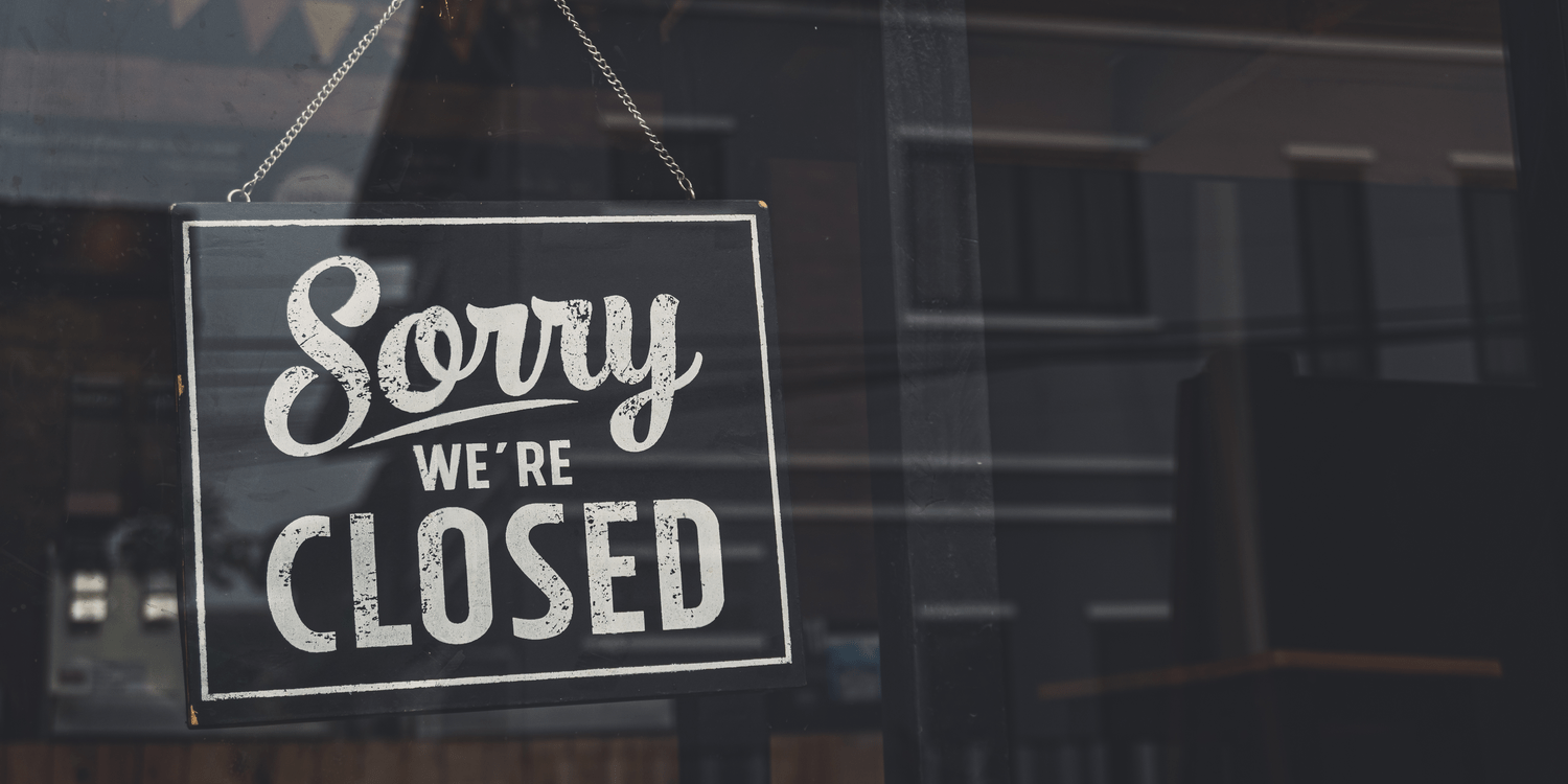 Black sign with white lettering hanging in a shop window displaying the words 'Sorry we're CLOSED'.