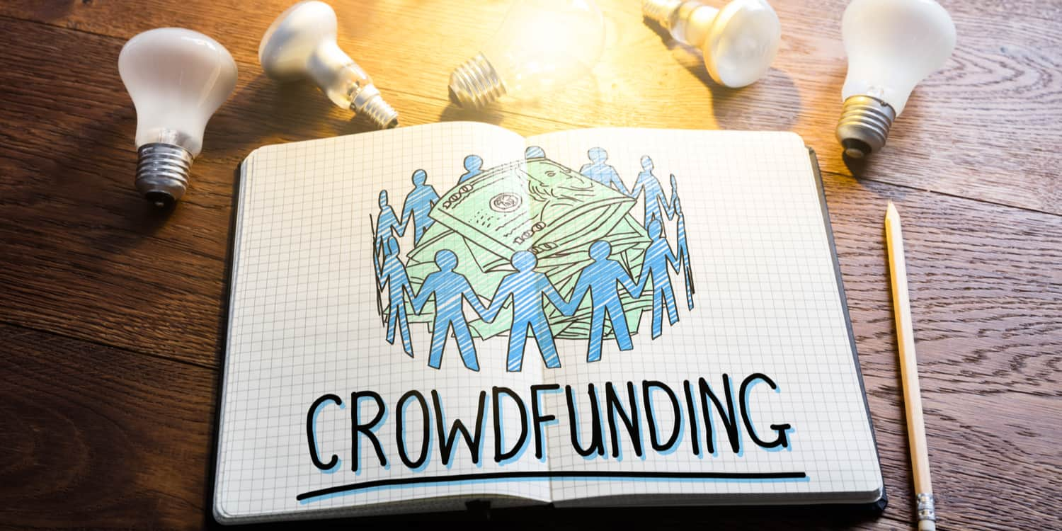 Book lying open with the an image depicting the crowdfunding concept and title 'CROWDFUNDING' with light bulbs lying beside the book.