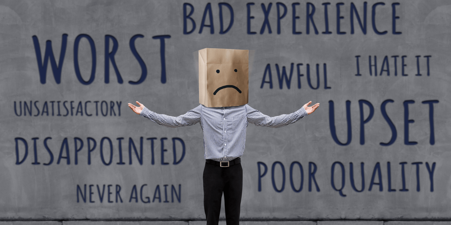A businessman standing with arms raised to the side and with a brown paper bag over his head. The paper bag has an unhappy face drawn on it. The wall behind the man is full of words of complaint, e.g. worst, upset, disappointed.