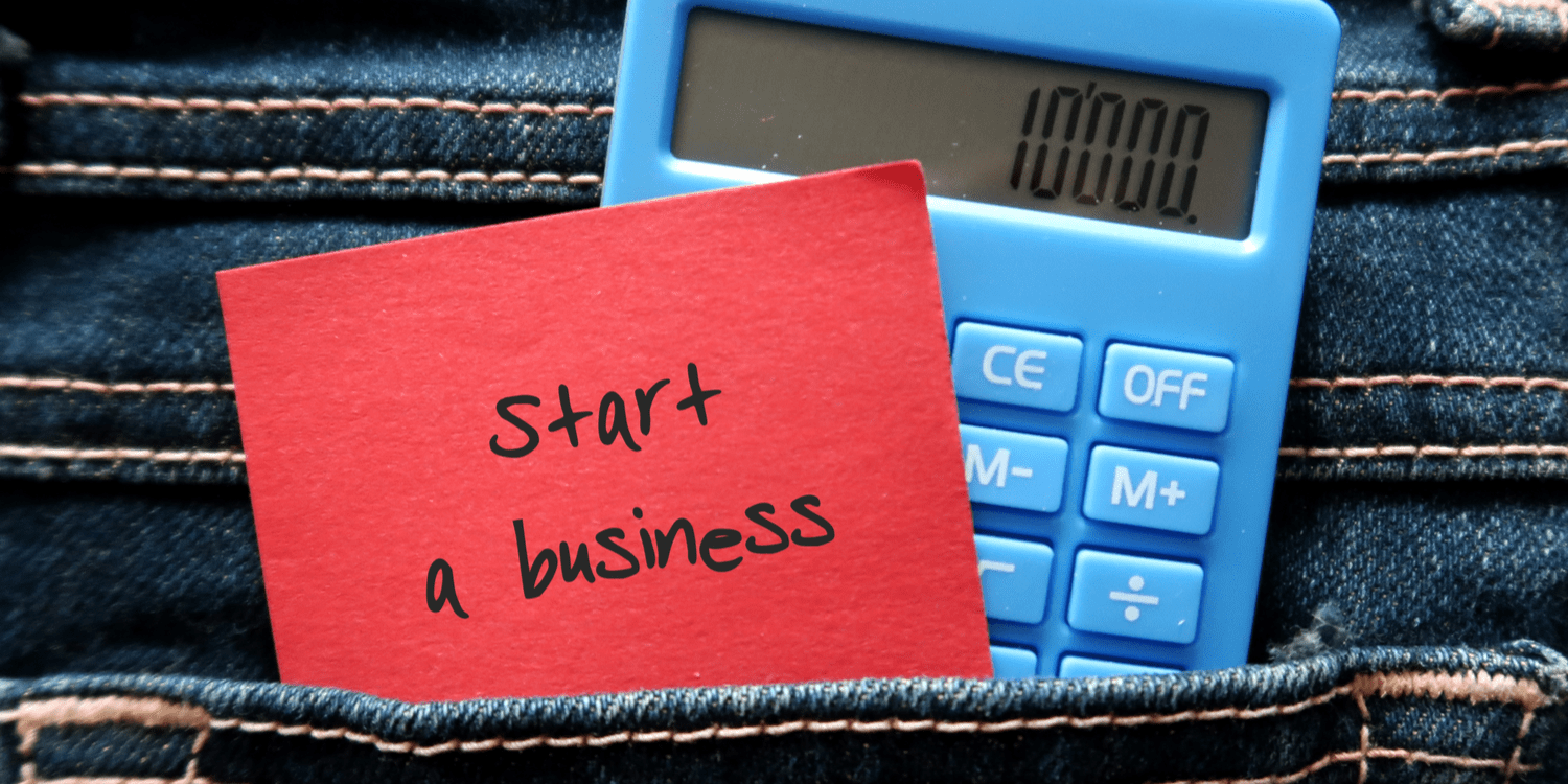 Red note and blue calculator in jeans pocket written START A BUSINESS , concept of a new small business owner calculating the startup cost to launch business on their own