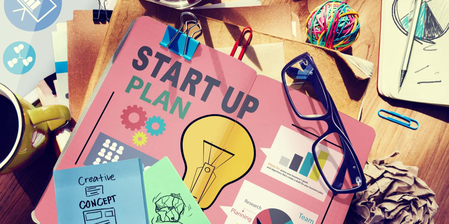 Desktop with start up plan and other strategy documents, illustrating starting a side business concept.