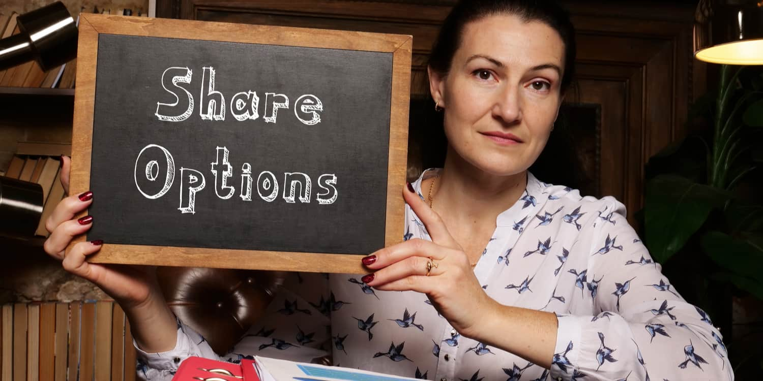Image of a female employee holding up a blackboard with 'Share Options' displayed in white chalk.
