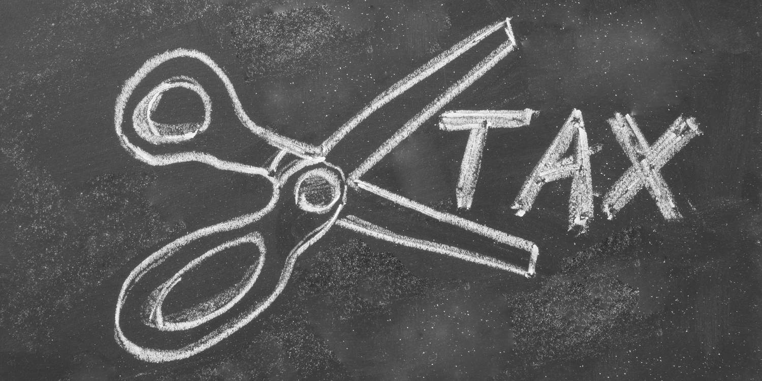 Scissors and the word TAX drawn on a blackboard in white chalk.