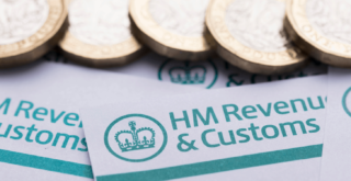 Pound coins sitting on top of HM Revenue & Customs forms.