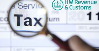 Magnifying glass held over an HMRC tax return form, highlighting the word 'Tax'.